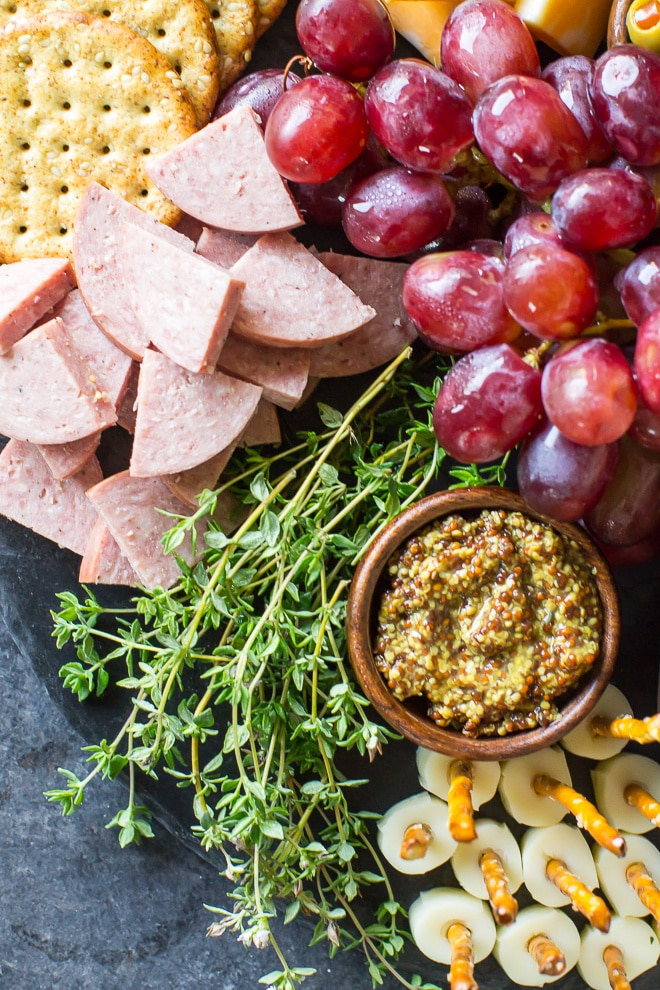 A Midwest Charcuterie Platter ripe with regional offerings including braunschweiger, venison sausage, mozzarella pretzel sticks, and ham and pickle roll ups. All the best Midwestern snacks on one delicious cheeseboard!