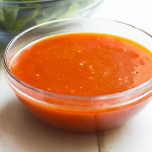French dressing in a clear dressing dish.