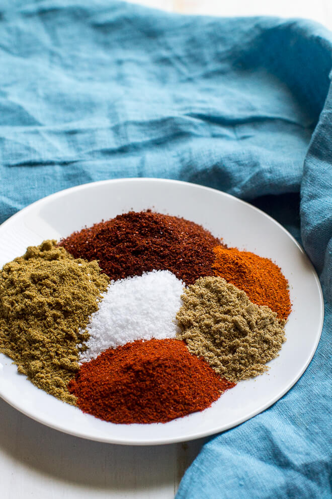 Homemade Taco Seasoning - a photo of six spices on a white plate on a blue cloth background - click photo for full written recipe