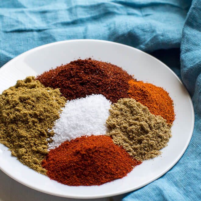 A white plate with piles of the colorful seasonings that constitute the taco seasoning mix: chili powder, cayenne, ground coriander, paprika, and ground cumin. In the center there is a pile of white salt.