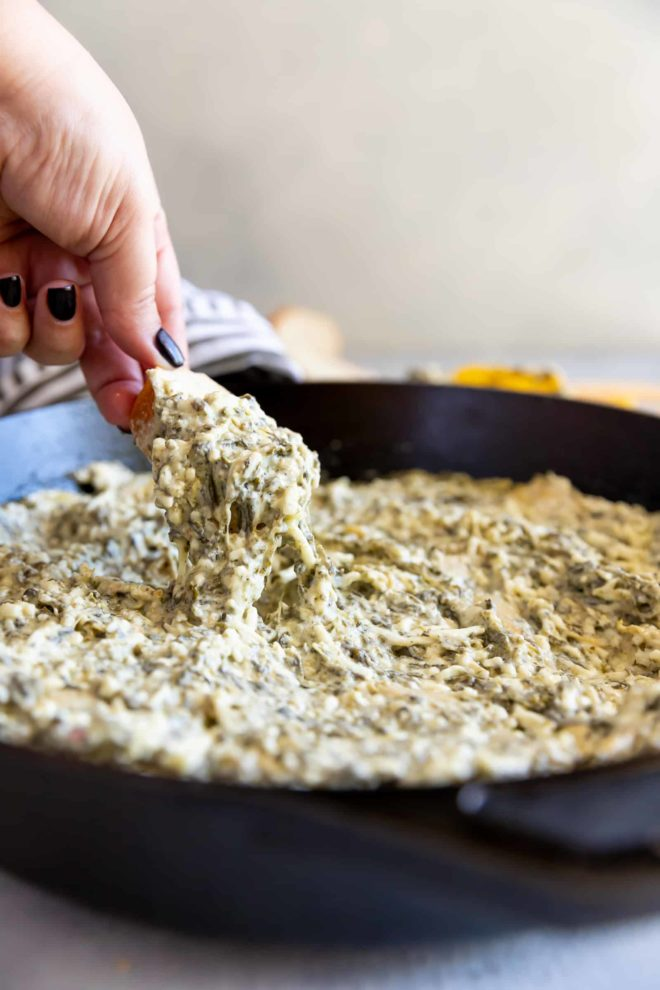 Spinach and artichoke dip being scooped out of a black cast iron pan.