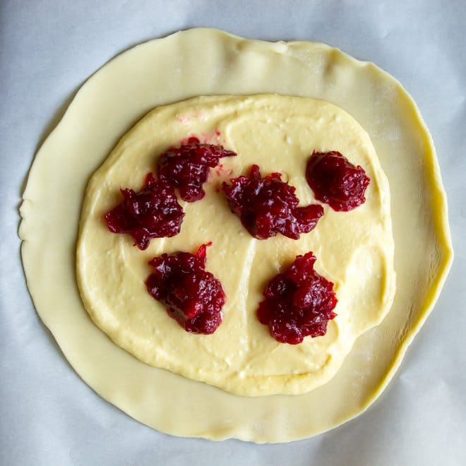 This Cranberry Cheesecake Galette is an easy free-form tart (from store-bought pie crust!) filled with fresh cranberry sauce and a rich, cheesecake filling!