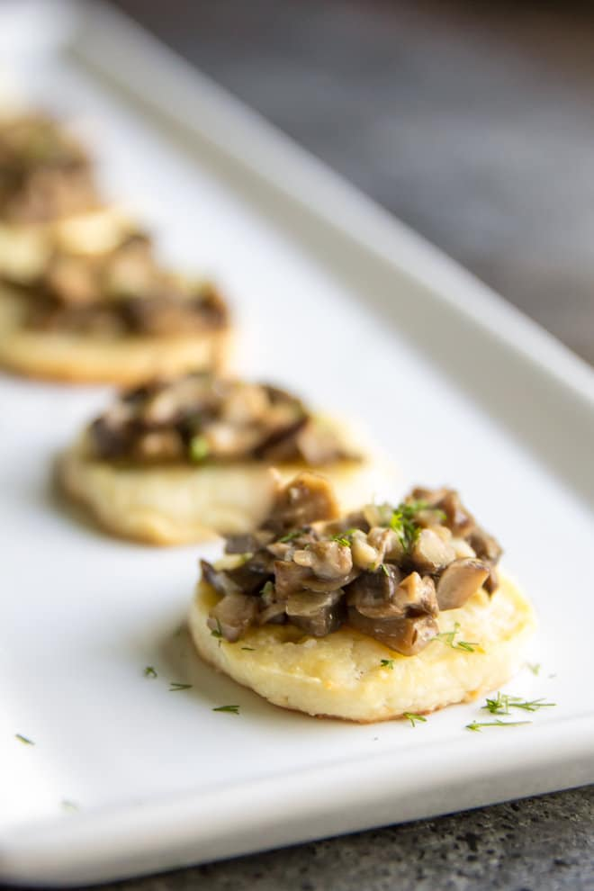 Homemade Cream Cheese Crisps with Mushroom Ragout on a white platter.