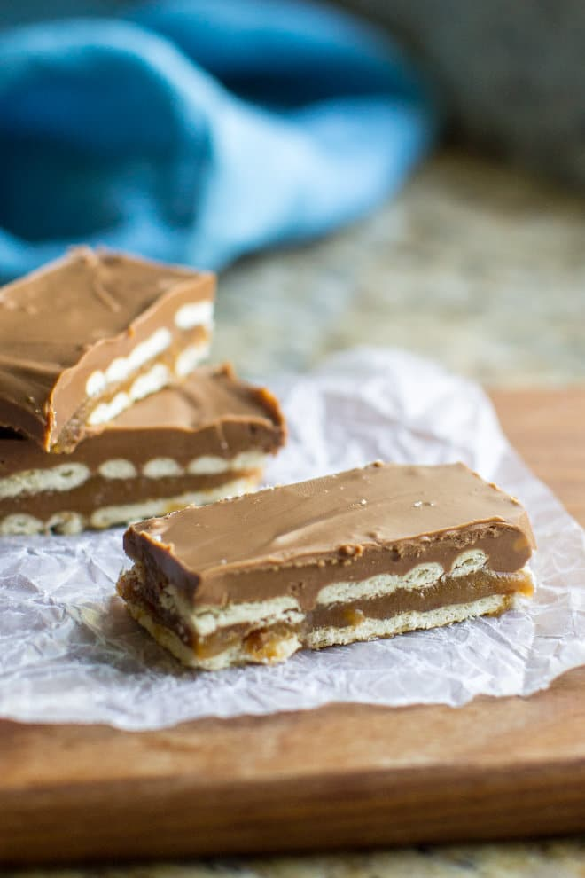 Homemade Twix Bars on parchment paper sitting on a cutting board.