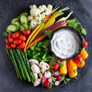 Easy dill dip in a dish on a plate with various vegetables.