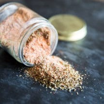 A photo of a clear spice jar on it's side pouring out the homemade cajun seasoning blend. It is on a dark countertop and the jar's gold lid is in the background, slightly out of focus.