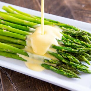 Hollandaise sauce being poured onto asparagus on a white serving platter.