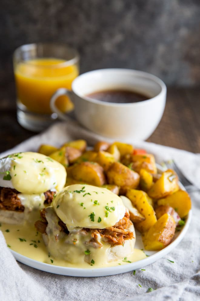 Pulled Pork Eggs Benedict is the ultimate breakfast experience. Barbecue pulled pork, English muffins, poached eggs, and plenty of Hollandaise!