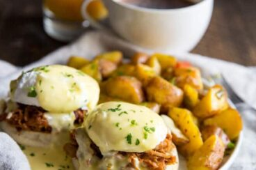 Pulled Pork Eggs Benedict on a white plate with a side of potatoes.