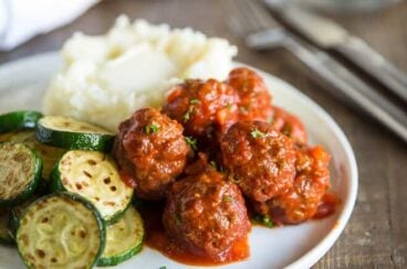 Slow Cooker Meatloaf Meatballs on a white plate with a side of mashed potatoes and roasted sliced cucumbers.