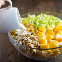 Dressing being poured onto a Waldorf Salad in a clear bowl.