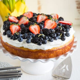 A luscious Lemon Yogurt Cake topped with a sweet lemony glaze, Limoncello whipped cream, and plenty of fresh berries. Perfect for dessert or brunch!