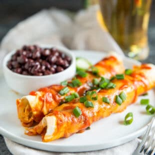 Sriracha Chicken Enchilada on a white plate with a side of black beans.