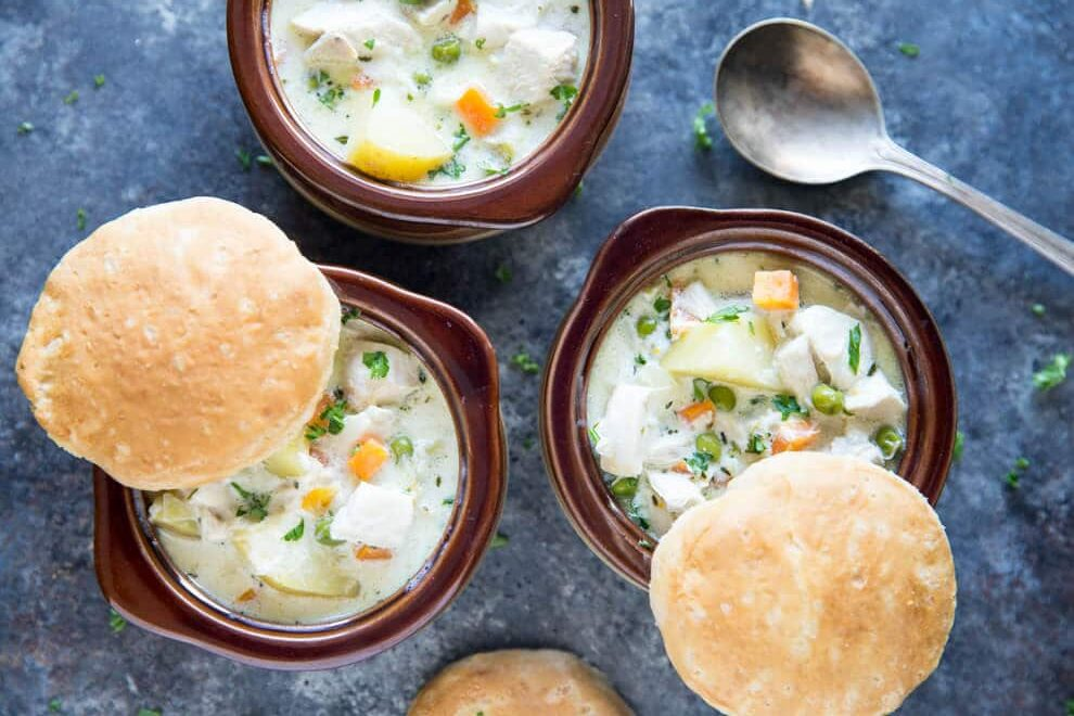A portrait shaped photo of three bowls of chicken pot pie soup with carrots, peas, and potatoes in a creamy sauce with three freshly made biscuits vidisble. There is a spoon in the lower right hand corner. the bowls are brown on a blue background.
