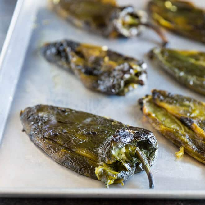 Roasted poblano chiles that have been skinned and seeded on a sheet pan.