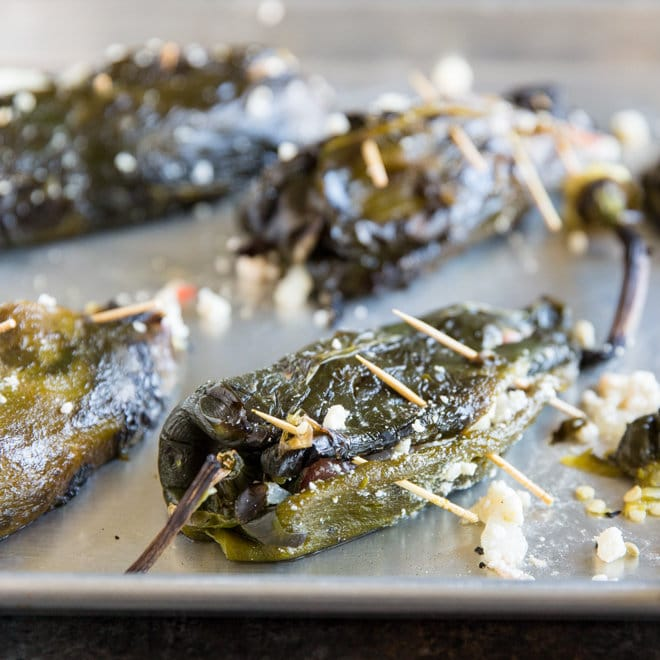 Roasted poblano chiles stuffed with a two-cheese filling and secured with toothpicks on a sheet pan.
