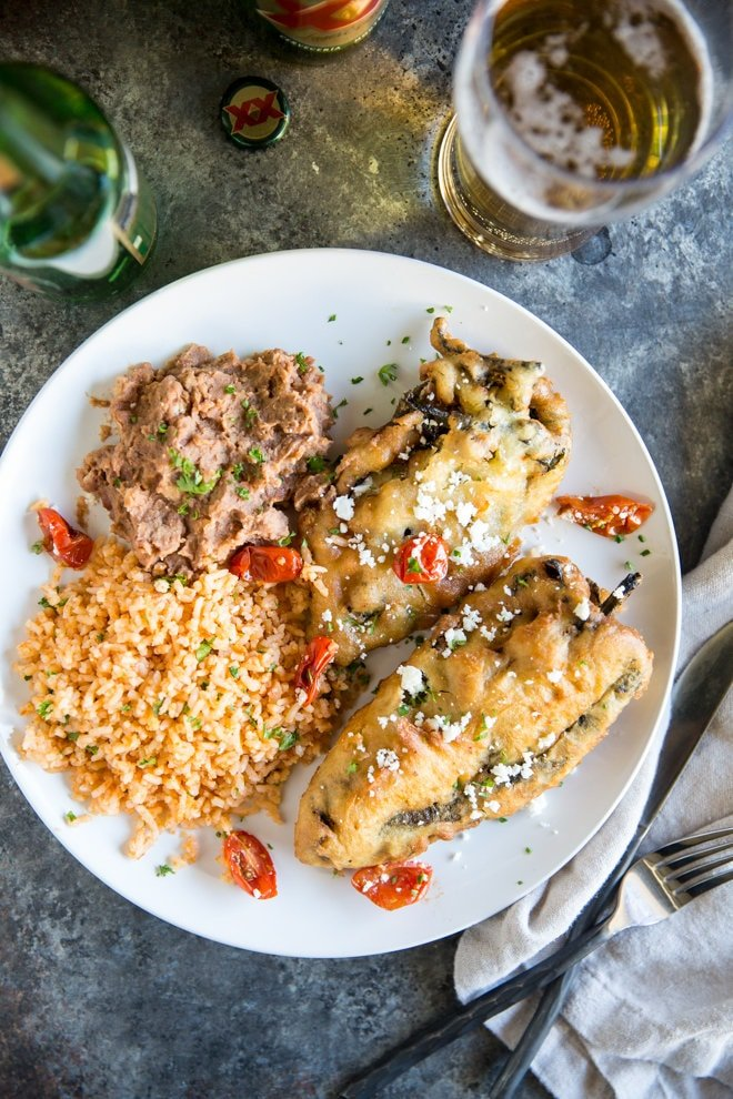 Overhead shot of two freshly fried chile rellenos with Mexican Rice and refried beans on a white plate with Dos Equis beer bottle in the background. Half the beer is poured into a glass.