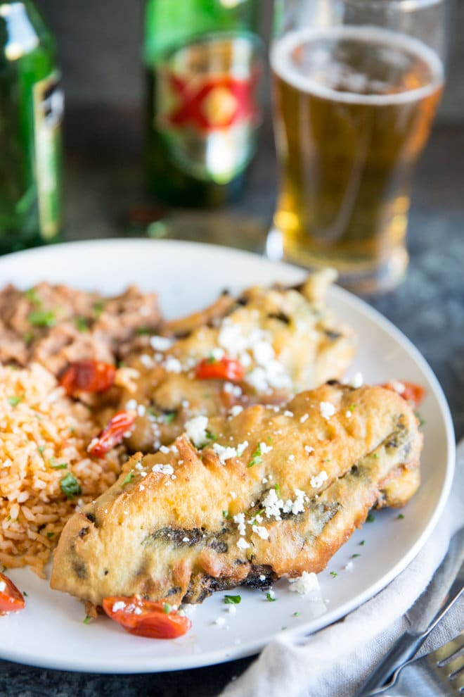 Two freshly fried chile rellenos with Mexican Rice and refried beans on a white plate with Dos Equis beer bottle in the background. Half the beer is poured into a glass.