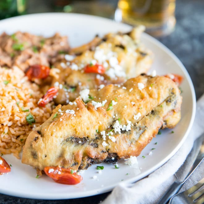 A square image of two freshly fried chile rellenos with Mexican Rice and refried beans on a white plate with Dos Equis beer bottle in the background. Half the beer is poured into a glass.