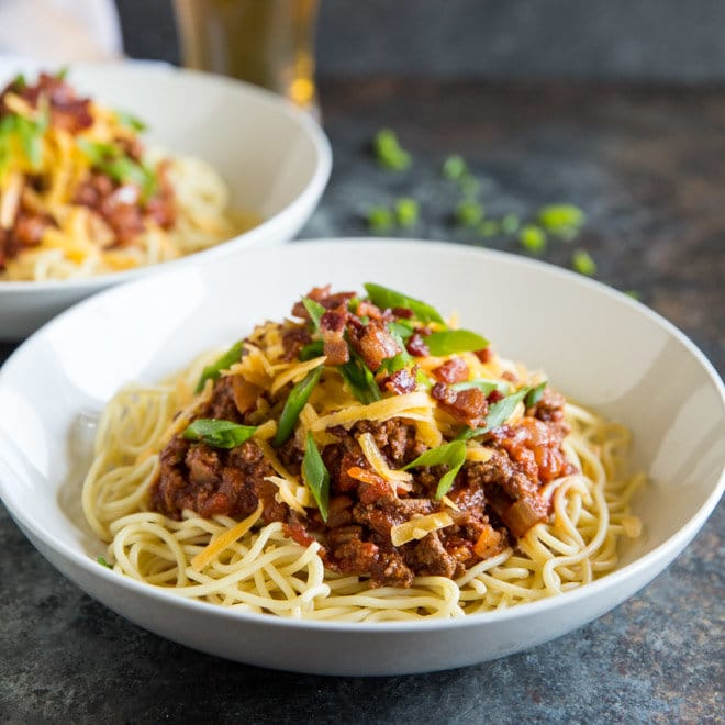 A square photo of two white bowls of Cowboy Spaghetti - chunks of ground sirloin, ,fire roasted tomatoes, fresh chopped green scallions and cheddar cheese - all topped with crumbled bacon. There is a beer visible out of focus in the back in a lager glass, and green scallions out of focus in the background net to the white bowl.
