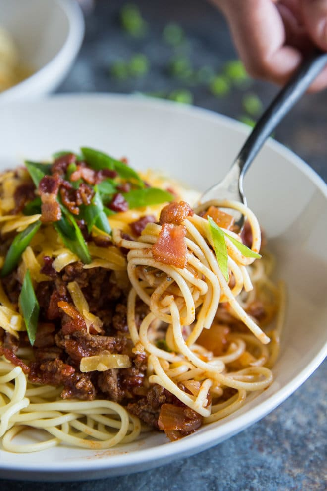 A portrait photo of a white bowl of Cowboy Spaghetti - chunks of ground sirloin, ,fire roasted tomatoes, fresh chopped green scallions and cheddar cheese - all topped with crumbled bacon. There is a fork with swirled cowboy spaghetti in the center-right of the photo.