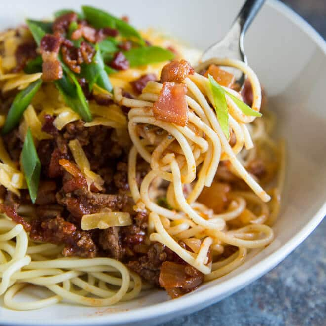 A square photo of a white bowl of Cowboy Spaghetti - chunks of ground sirloin, ,fire roasted tomatoes, fresh chopped green scallions and cheddar cheese - all topped with crumbled bacon. There is a fork with swirled cowboy spaghetti in the center-right of the photo.