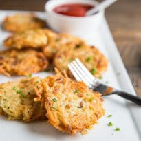 A square photo of seven golden brown extra crispy potatoe latkes on a white rectangle plate. There is a silver fork on the right of the photo, resting again the edge of the plate, and a small white bowl filled with ketchup is in the backround. There is a small white serving spoon in the bowl.