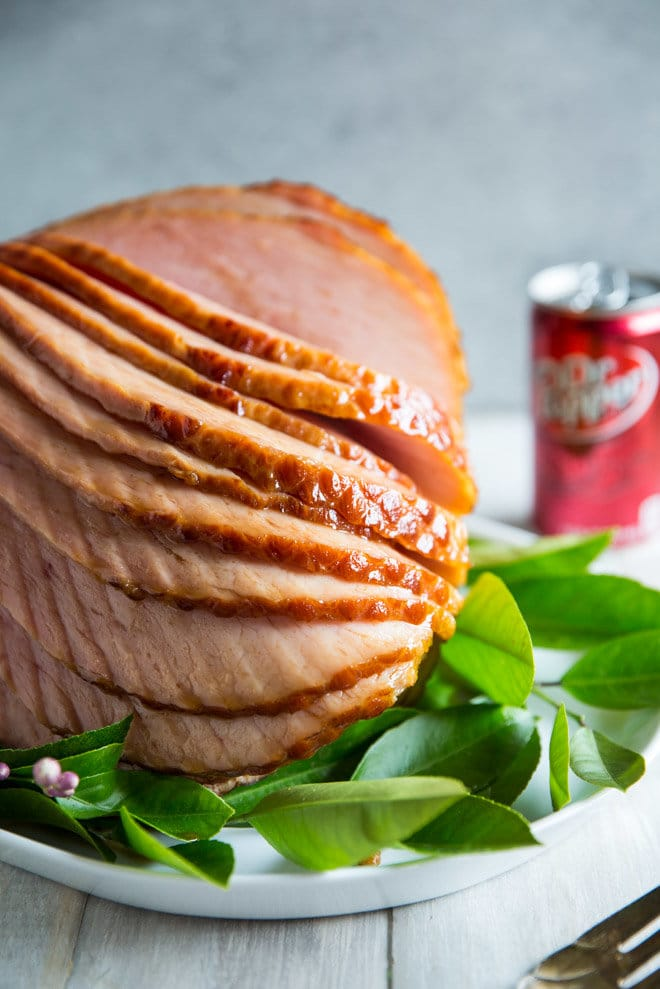 A portrait photo of Dr. Pepper Ham. The ham is spiral cut and nine of the slices are stacked forward, showing the spiral cut marks and showing the sweet glaze created using Dr. Pepper. The ham is surrounded by lemon leaves and tehre are four lemon blossoms visible in the lower left hand corner. There is a can of Dr. Pepper visible in the right background. The ham is on a white serving platter and there is a silver serving fork in the foreground in the right corner.