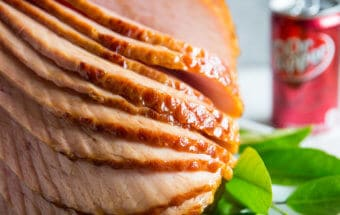 A square photo of Dr. Pepper Ham. The ham is spiral cut and nine of the slices are stacked forward, showing the spiral cut marks and showing the sweet glaze created using Dr. Pepper. The ham is surrounded by lemon leaves and tehre are four lemon blossoms visible in the lower left hand corner. There is a can of Dr. Pepper visible in the right background.