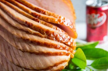 Dr. Pepper Ham spirally cut on a white serving platter with sprigs of green leaves.