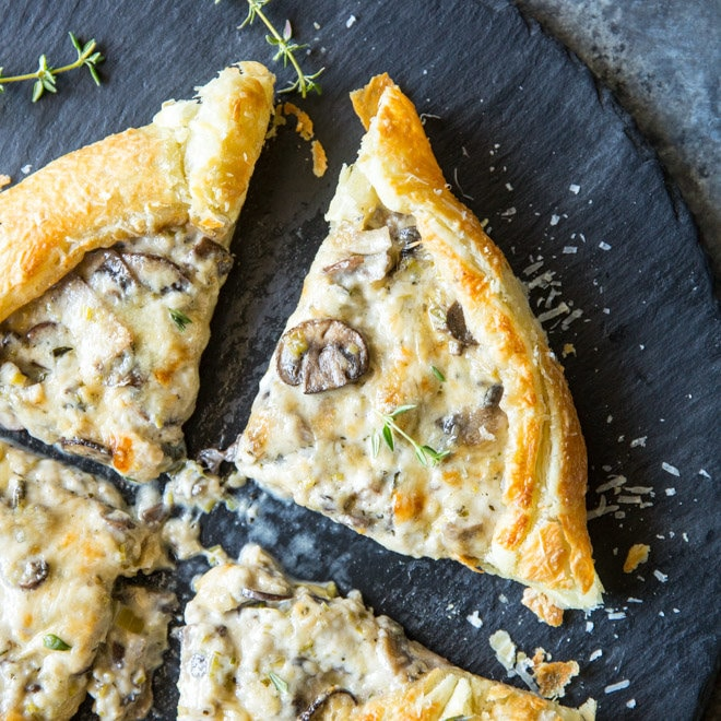 A square photo of four slices of a square soft and buttery mushroom and leek tart, topped with fresh green thyme and freshly grated Parmesan cheese. Beautifly browned mushrooms with cheese filling inside a golden brown pastry puff shell.