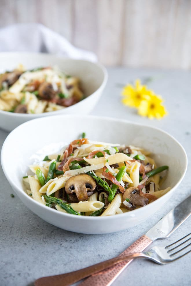 Pasta with Asparagus, Mushrooms, and Prosciutto in two white bowls.