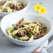 A square photo of two white bowls with delicious penne pasta, asparagus, mushrooms, and prosciutto. There is a fok and knif next to the foremost bowl, and a yellow flower out of focus in the background.