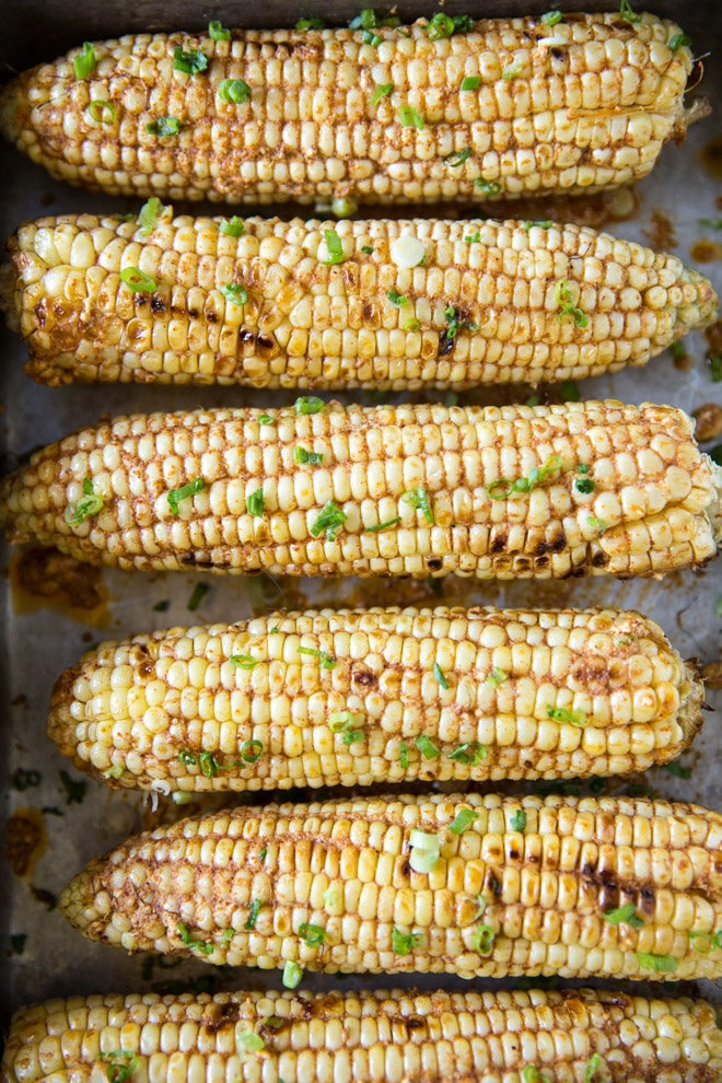 Four cobs of corn with seasoning on them.