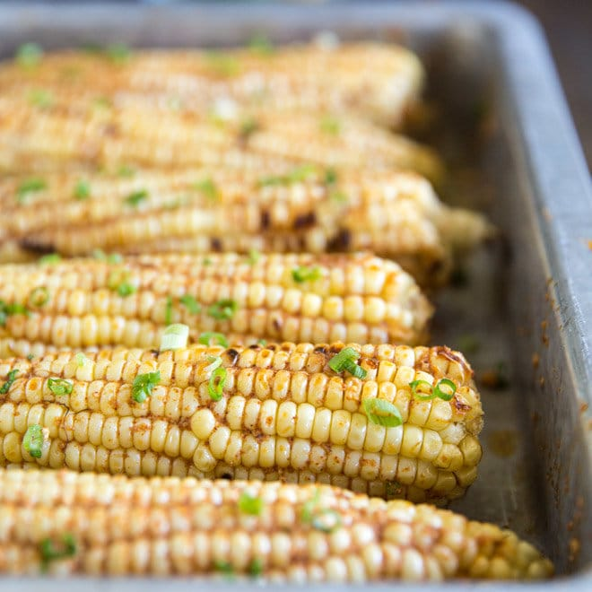 Corn on the cob with spices on top.