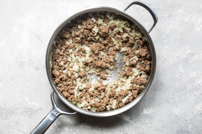 Cooked ground beef and onions in a skillet.