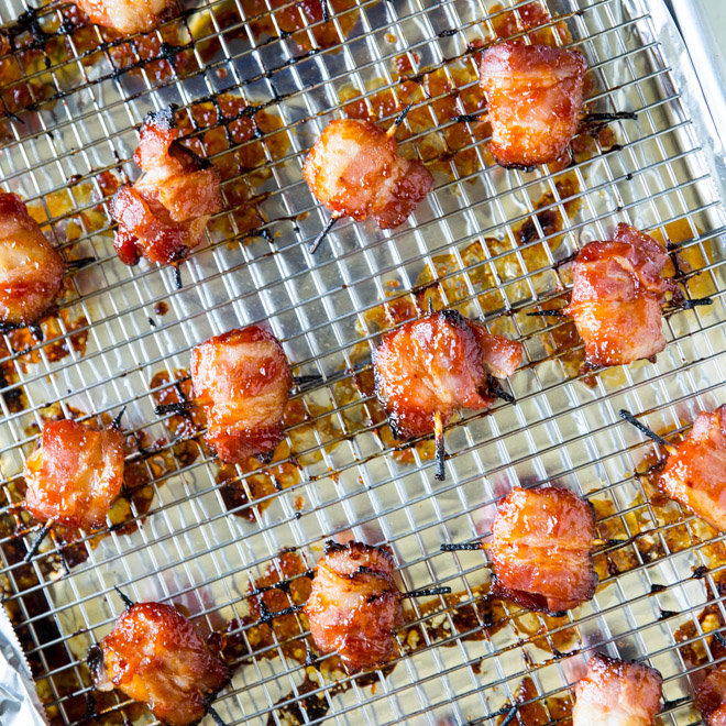 Bacon Wrapped Water Chestnuts on a cooling rack placed on a baking sheet.