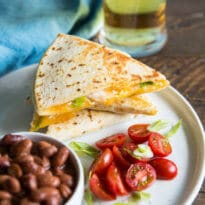Sriracha Chicken Quesadillas on a white plate with a side of beans and cherry tomatoes.