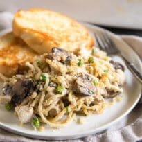 Turkey Tetrazzini casserole on a white plate with slices of toasted bread and a fork.
