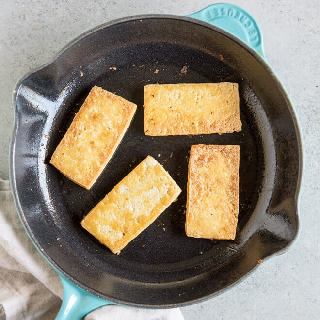 Tofu being browned on a black skillet.