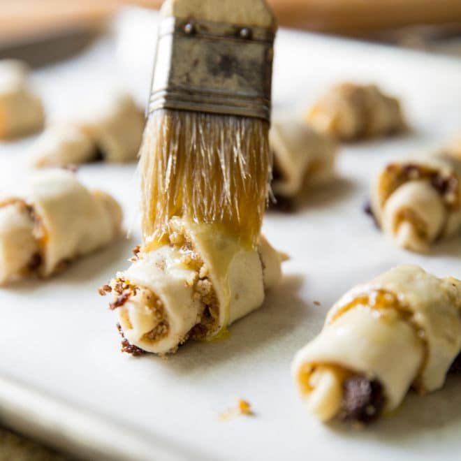 An easy Rugelach recipe with cream cheese in the dough and a filling of apricots, raisins, and walnuts. You'll love these crispy little cookies!