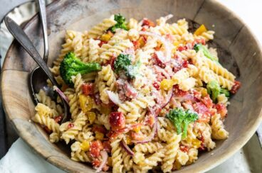 Easy cold pasta salad with a serving spoon and fork in a wooden bowl.