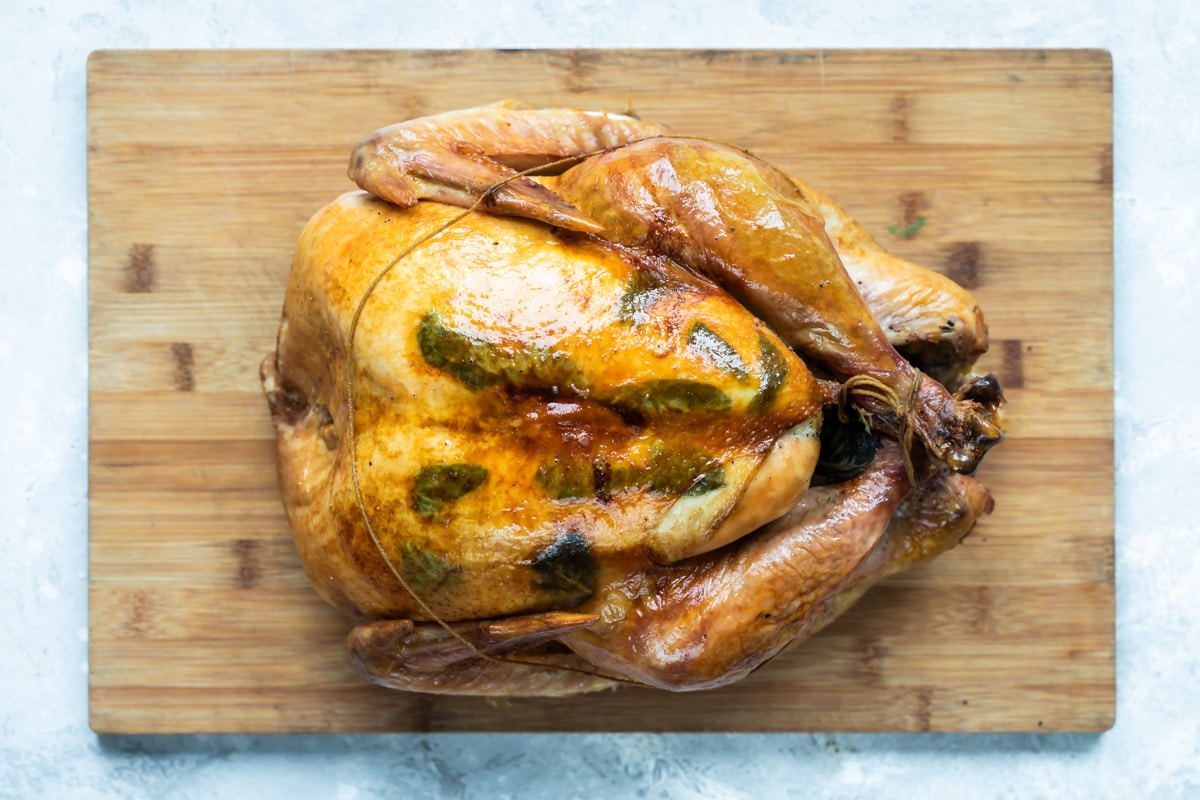A trussed, roasted turkey resting on a cutting board.