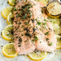 Baked salmon on a white platter.
