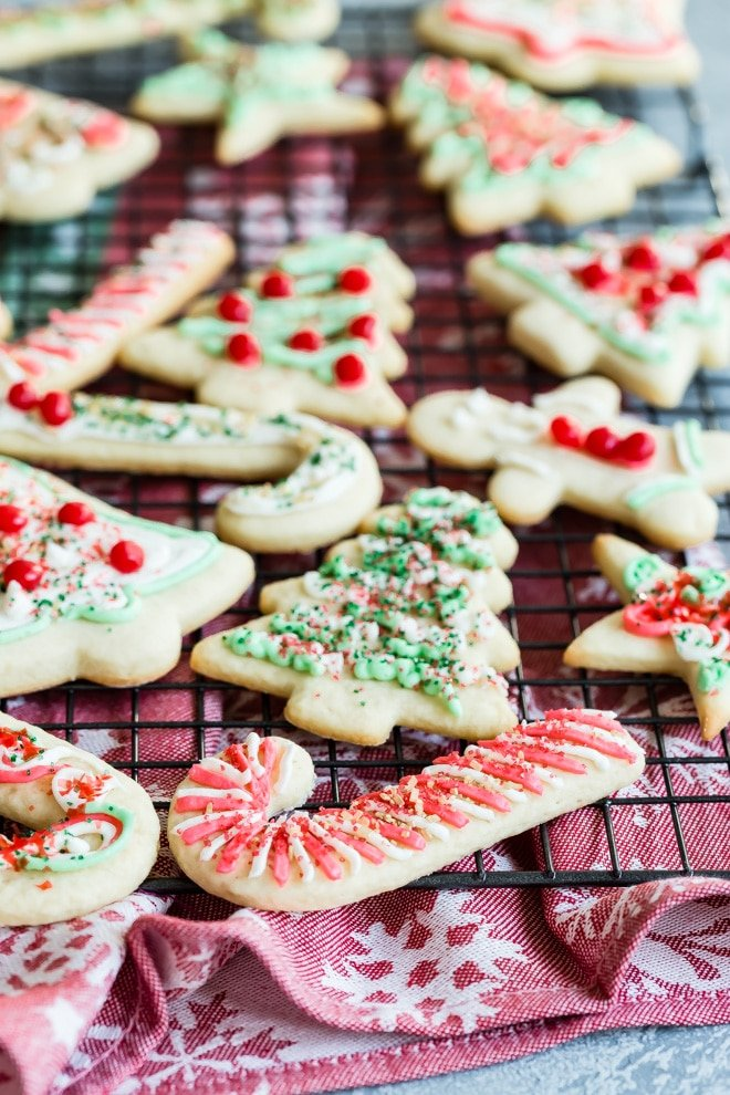 Frosted Christmas sugar cookies on a cooling rack.