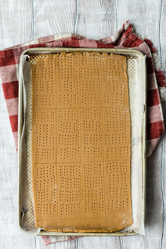 Homemade Graham Crackers - a photo of uncooked graham crackers on a silver cooking sheet with white wood and a white and red cloth - click photo for full written recipe