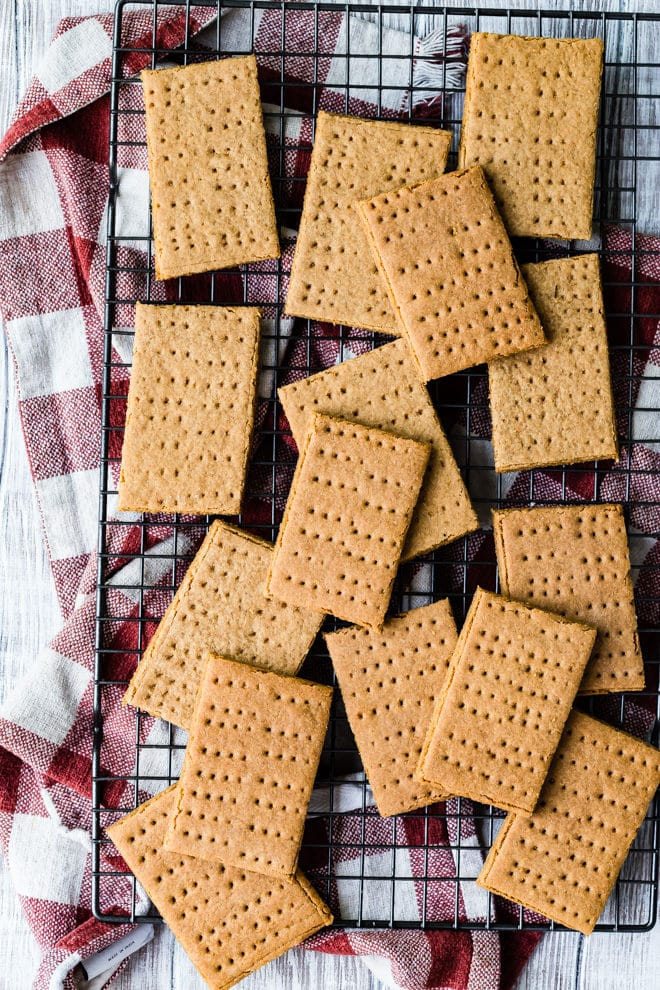 Homemade Graham Crackers - a bird's eye view photo of multiple brown crackers on a black wire rack over a red and white cloth on a wooden background - click photo for full written recipe