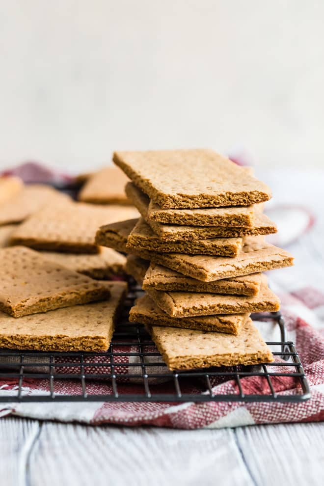 Homemade Graham Crackers - a side view photo of multiple brown crackers on a black wire rack over a red and white cloth on a wooden background - click photo for full written recipe