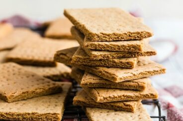 Homemade graham crackers stacked on a cooling rack.
