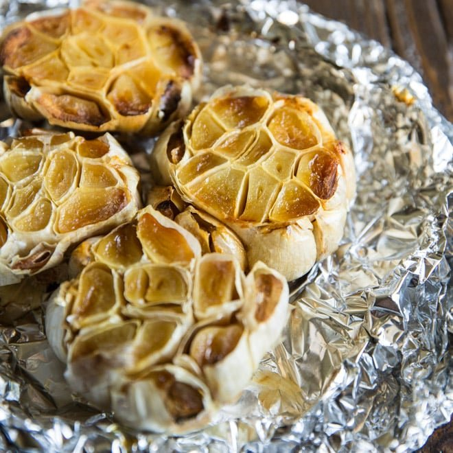 An easy recipe for how to roast garlic in the oven. Mash roasted garlic cloves and add to potatoes, soups, and salad dressings or spread directly on bread.